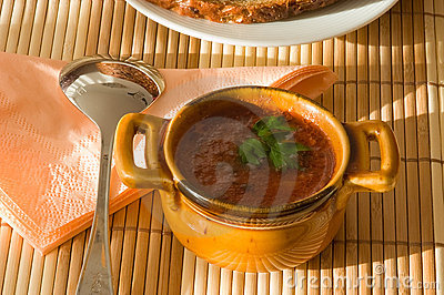 Taza de sopa del tomate en la servilleta de bambú.