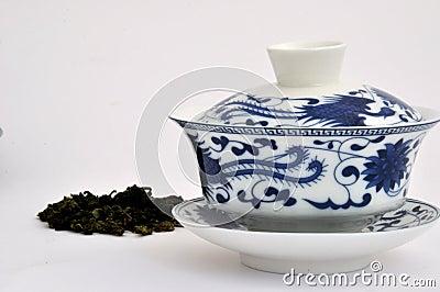Taza de té azul de la pintura del estilo chino y té sin procesar