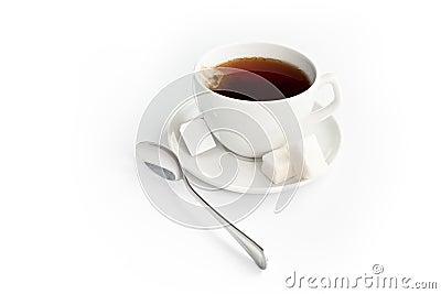 Taza de té con el azúcar y la bolsita de té aislados en blanco