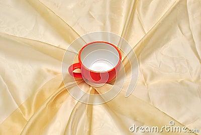 Taza roja en la pañería de oro de la tela