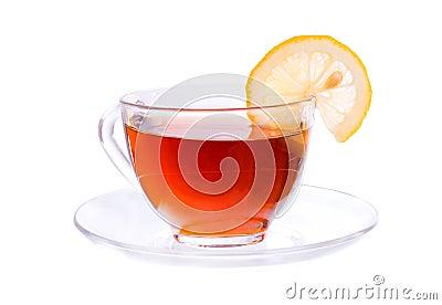 Taza transparente con el segmento del té y del limón