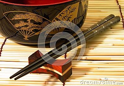 Tazón de fuente y palillos de madera