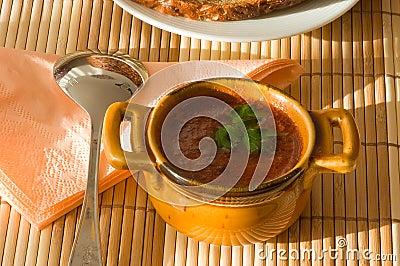 Tazza della minestra del pomodoro sul tovagliolo di bambù.