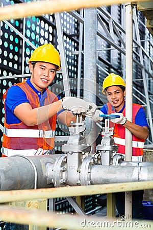 Técnicos o ingenieros asiáticos que trabajan en la válvula