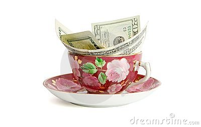 Tea cup with dollar bills isolated
