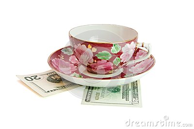 Tea cup and saucer on dollar bills isolated