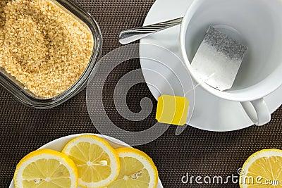 Tea cup, slices of lemon and brown sugar