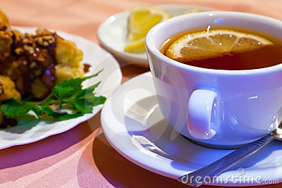 Tea with lemon and cakes