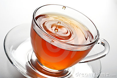 Tea splash in glass cup
