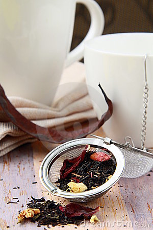 Tea strainer with a fragrant black tea and cups