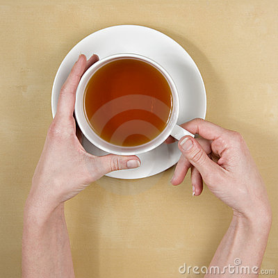 tea-top view of female hands holding a cup of tea