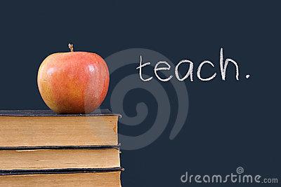 Teach written on blackboard with apple and books