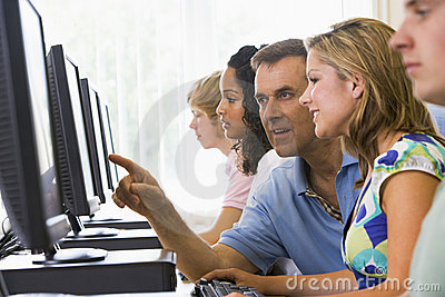 Teacher assisting college student in computer lab