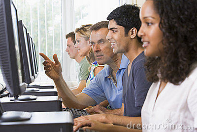 Teacher assisting college student on computers