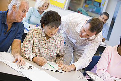 Teacher assisting mature student in class