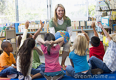 Teacher and children with hands raised in library