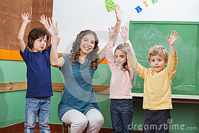 Teacher And Children With Hands Raised In