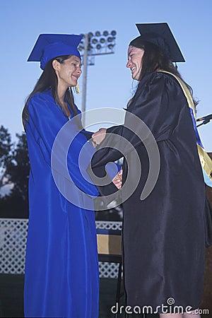 Teacher congratulates a high school graduate Editorial Stock Image