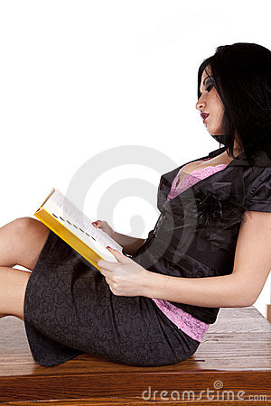 Teacher on desk reading book