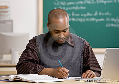 Teacher grading papers in school classroom