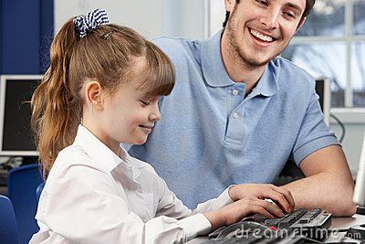 Teacher helping girl using computer in class