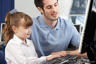 Teacher helping girl using computer in class