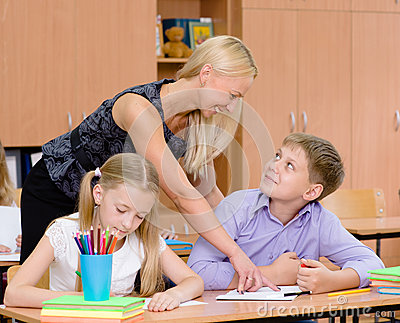 Teacher helping pupil explains how to solve the task Stock Photo