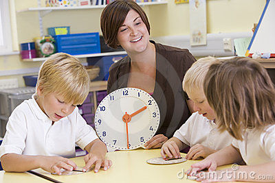 Teacher helping schoolchildren learn to tell time