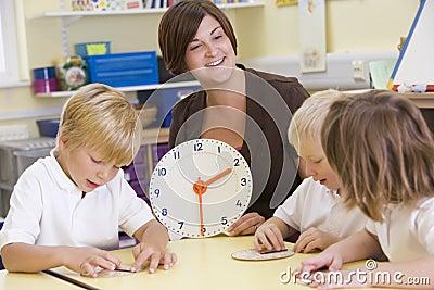 Teacher helping schoolchildren learn to tell time