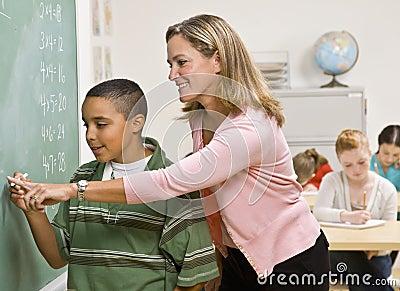 Teacher helping student at blackboard