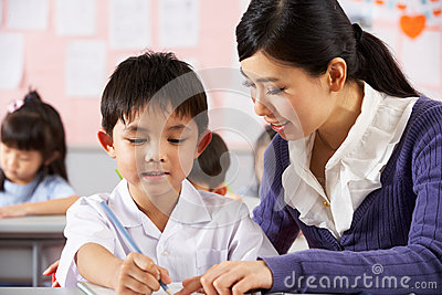 Teacher Helping Student In Chinese School