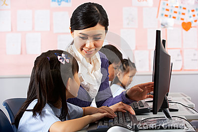 Teacher Helping Student During Computer Class