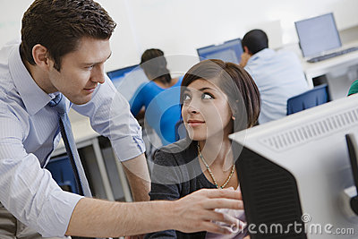 Teacher Helping Student In Computer Lab