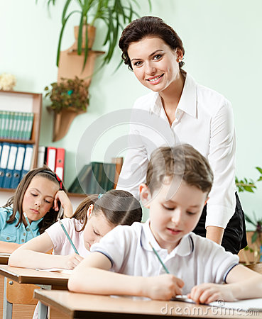 Teacher helps her pupils to do the task