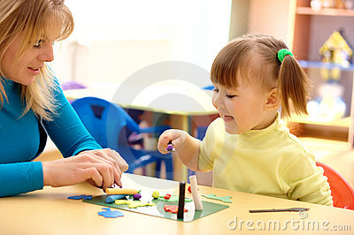 Teacher and little girl play with plasticine