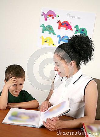 A teacher reads a book with her preschool student