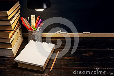 The teacher`s desk or a worker, on which the writing materials lie, a books, in the evening under the lamp. Blank for text or Stock Photo