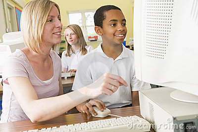 Teacher and schoolboy studying on a computer