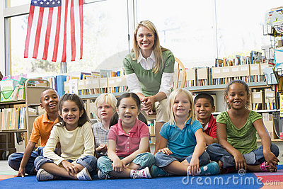 Teacher sitting with children in library