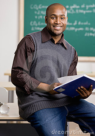 Teacher sitting on desk with text book