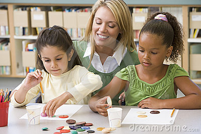 Teacher sitting with students in art class,