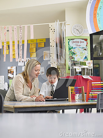 Free Teacher Sitting With Boy Using Laptop In Class Stock Photos - 31829253