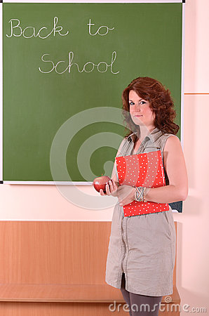 Teacher stand with book and apple in her hand