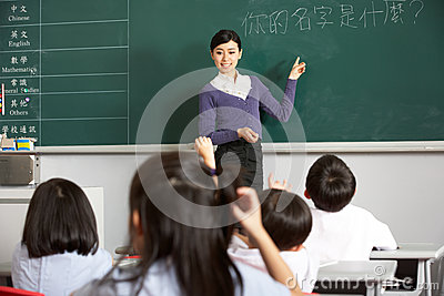 Teacher Standing By Blackboard In Chinese School