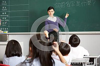 Teacher Standing By Blackboard In Chinese School