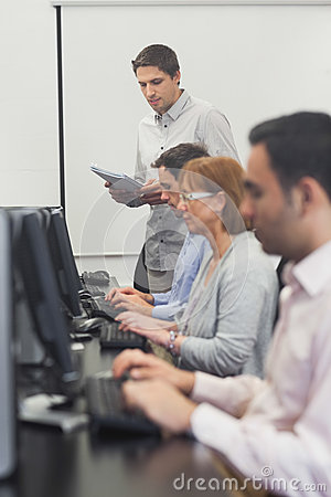 Teacher standing in front of computer class