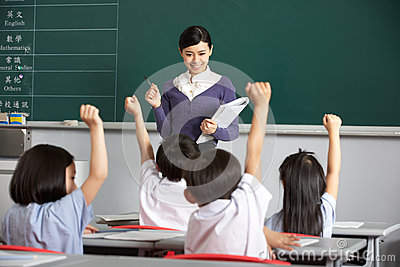 Teacher With Students In Chinese School Classroom