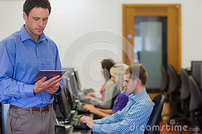 Teacher with students using computers in computer room