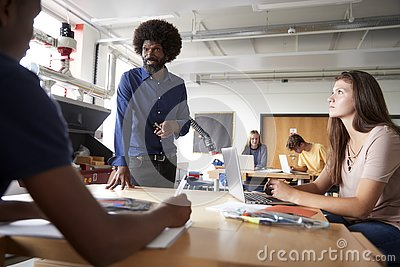 Teacher Talking To Group Of High School Students Sitting At Work Benches In Design And Technology Lesson Stock Photo