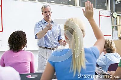 A teacher talks to school children in a class